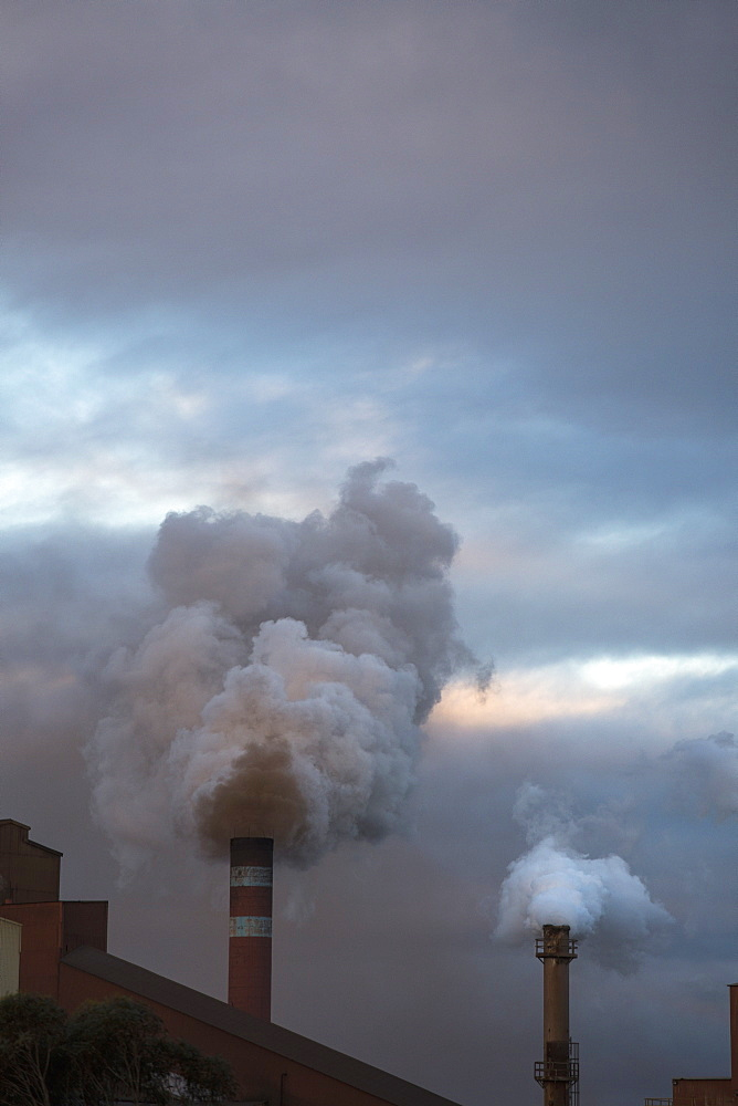 Smoke emitting from chimneys against cloudy sky