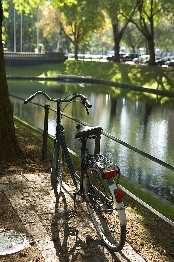 A old fashioned bicycle parked next to a river