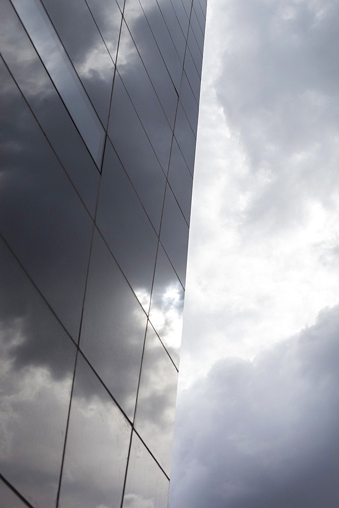 Glass building against cloudy sky