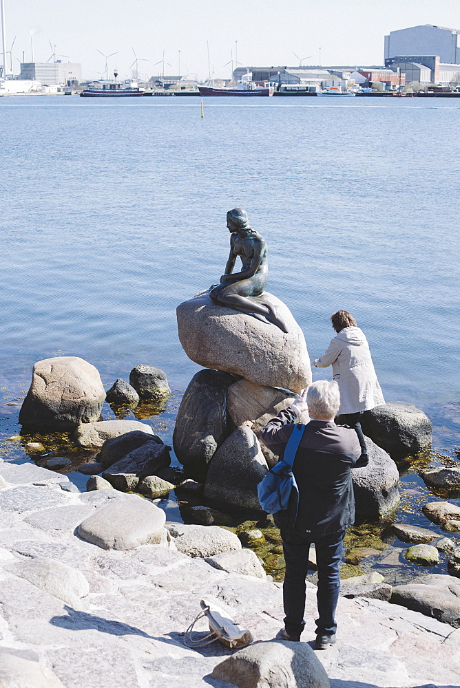 People at lakeshore with statue on rock