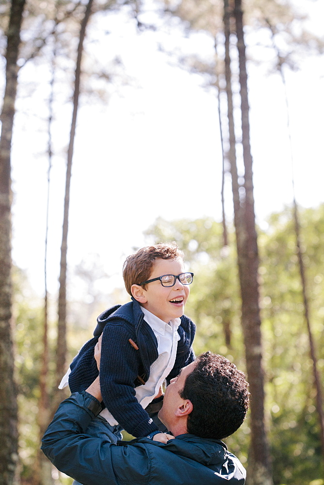 Happy man lifting boy in forest