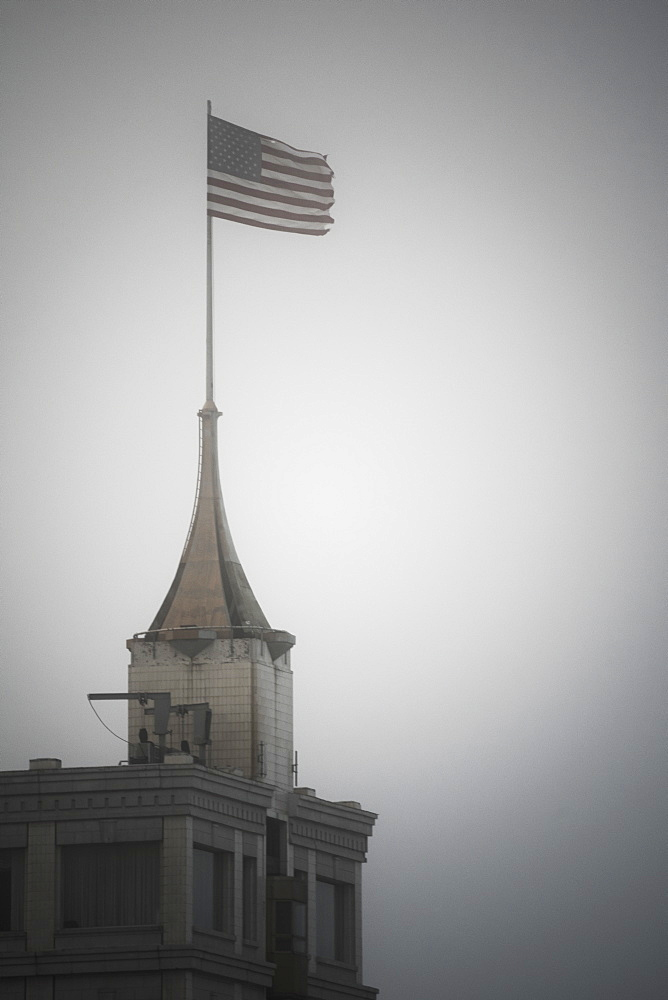 American flag on top of building against clear sky