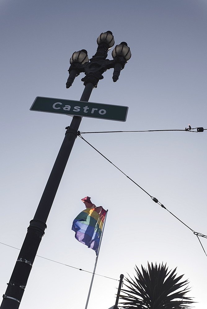Low angle view of Castro street sign and rainbow flag against clear sky