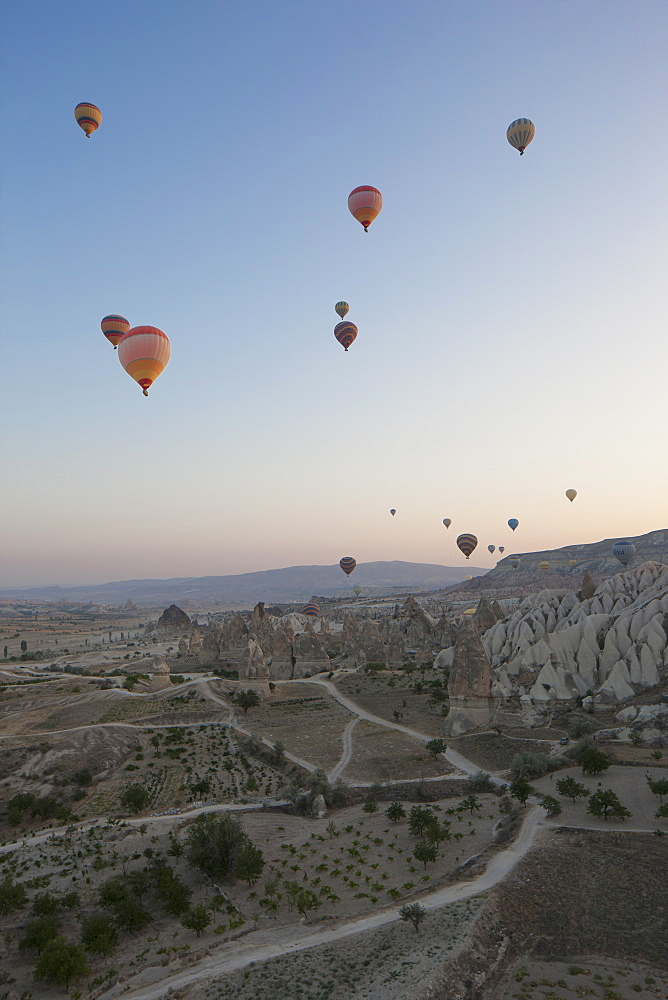 Hot air balloons flying over rocky landscape
