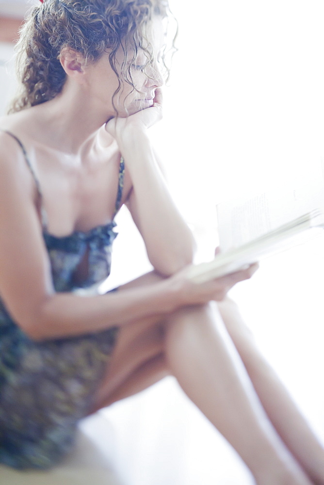 A woman sitting on a floor reading a book