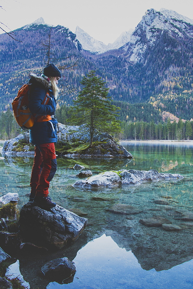 Side view of female hiker standing on rock at Lake Hintersee against mountains