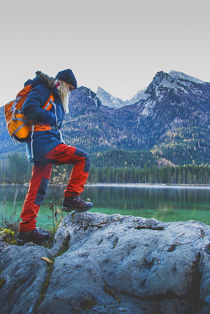 Side view of female hiker walking on rock against mountains