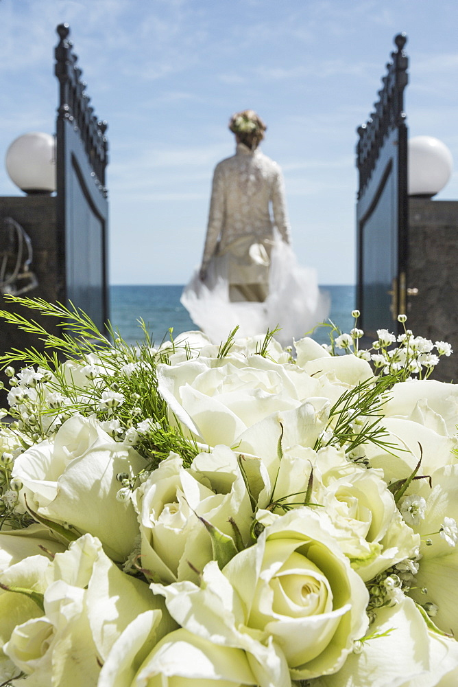Rear view of bride walking towards beach with focus on rose bouquet in foreground