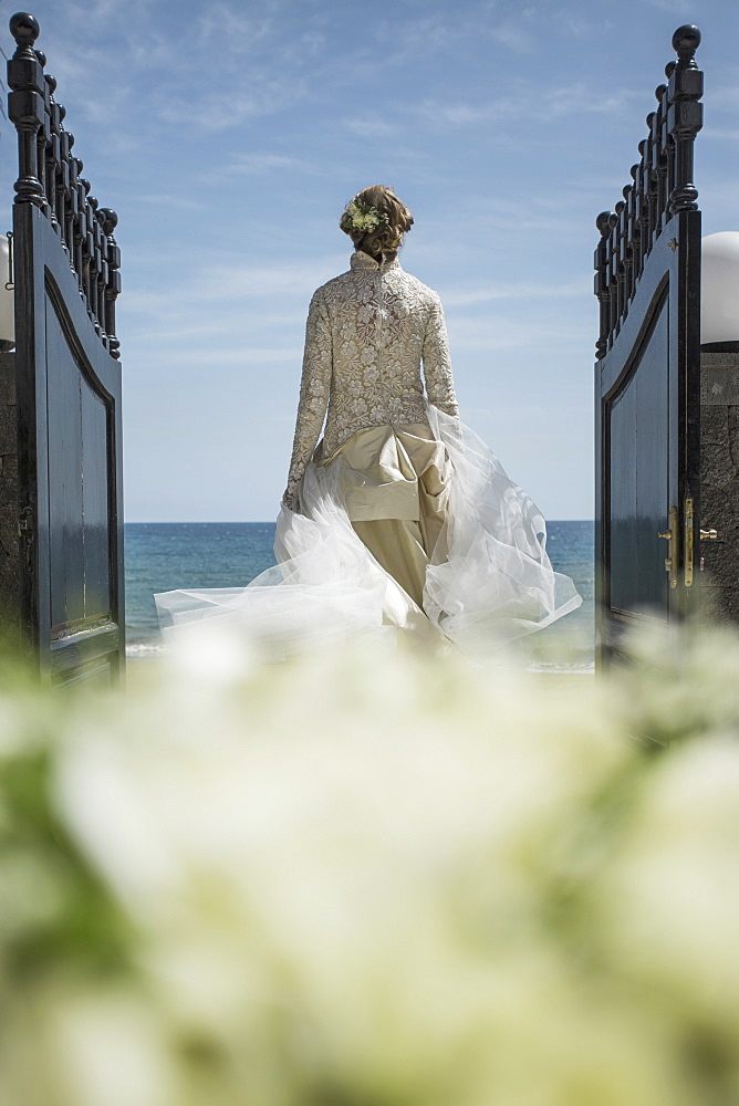 Rear view of bride walking towards beach