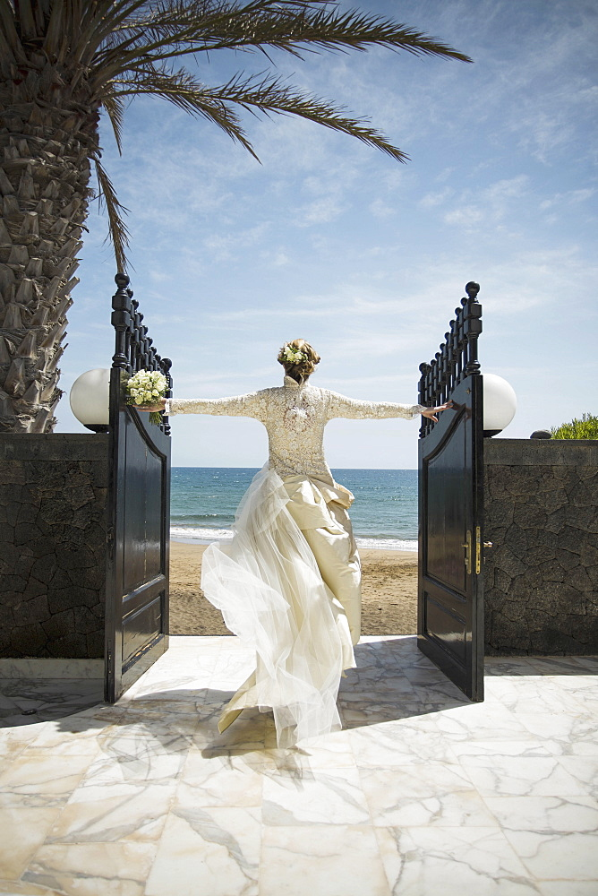 Rear view of bride opening gate while walking towards beach