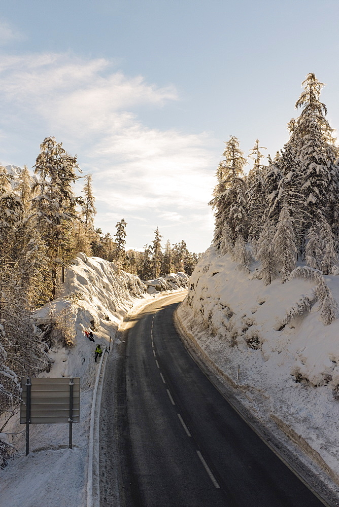 Mountain road amidst trees against sky during winter