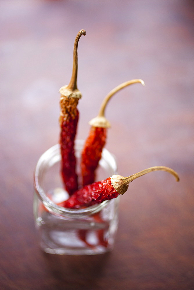 Three dried chilies in a glass jar