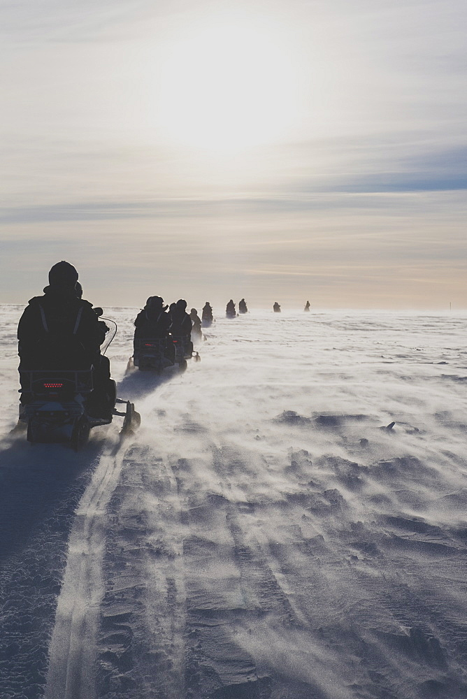 Rear view of people driving snowmobiles against sky on sunny day
