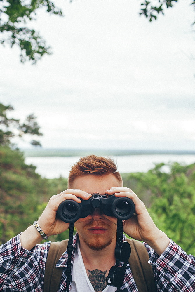 Close-up of young man with binoculars hiking at forest against sky