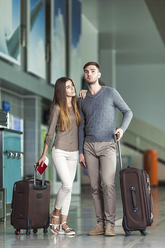 Full length of young couple with luggage waiting at airport