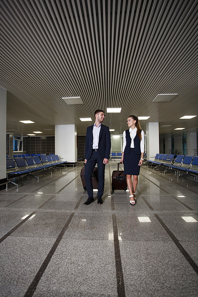 Full length of young businessman and businesswoman with luggage walking in airport