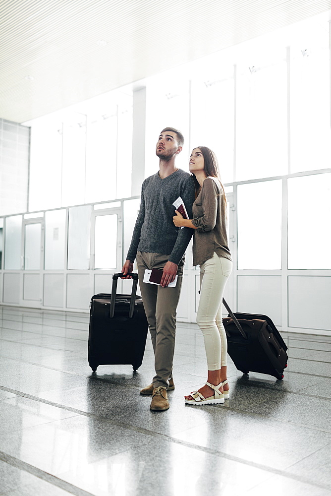 Full length of young couple with luggage and boarding passes at airport