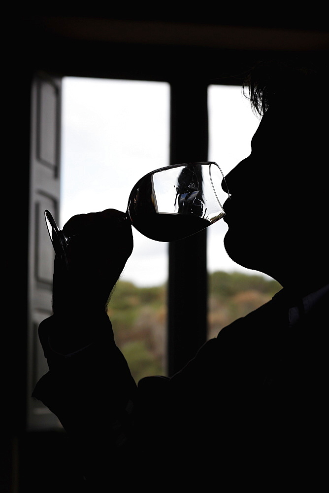 A man taking a sip of wine