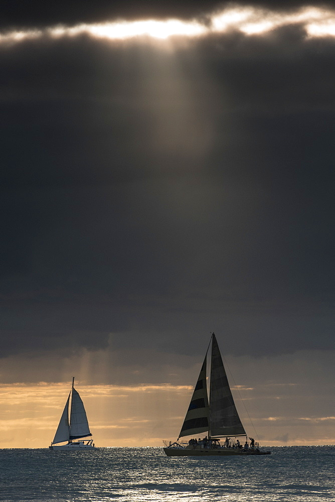 Boats sailing in sea against dramatic sky