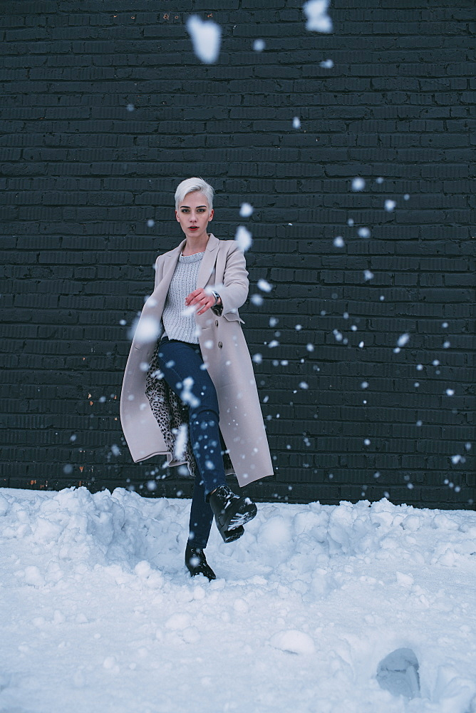 Portrait young woman kicking snow
