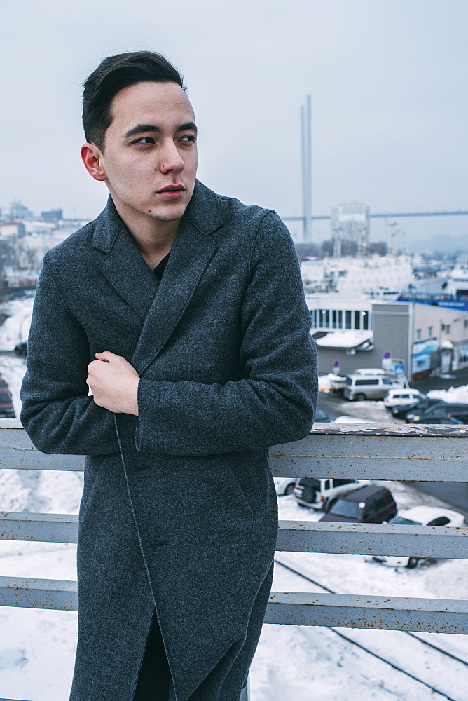 Young man in long coat on urban winter bridge