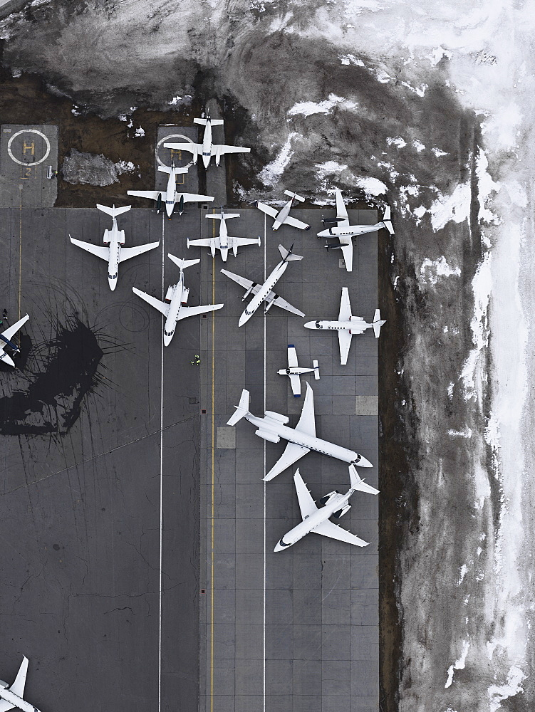 Aerial view private airplanes parked on tarmac surrounded by snow