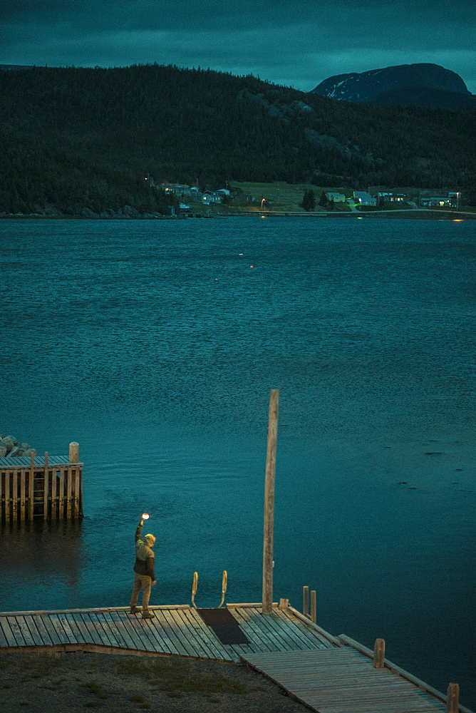 Detail of person standing on jetty by water, Gros Morne, Newfoundland, Canada