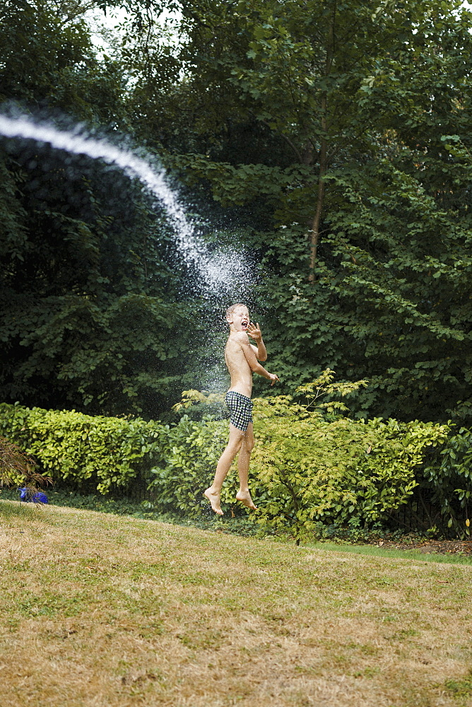Water spraying boy in swim trunks in backyard
