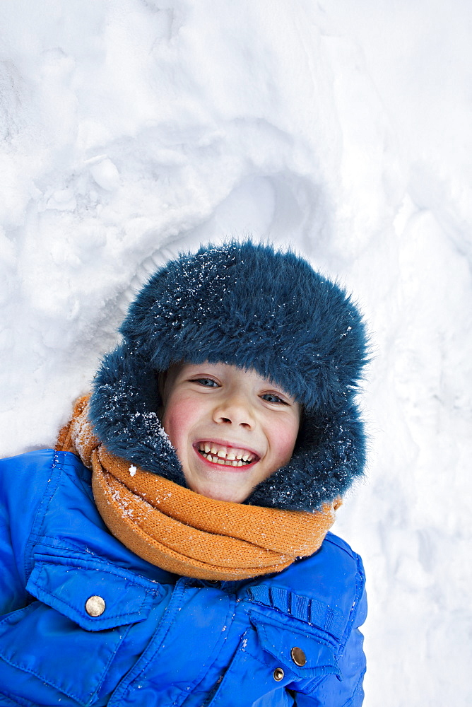 A young cheerful boy wearing warm clothing outdoors lying in the snow
