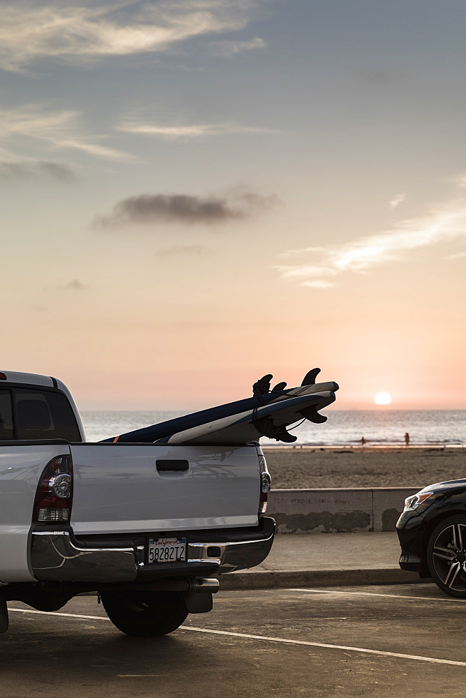 Surfboards in truck bed parked along beach at sunset, Newport Beach, California, USA