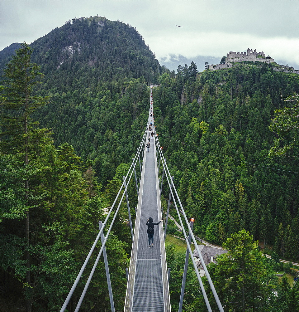 People walking across suspension bridge over green treetops, Tyrol, Austria