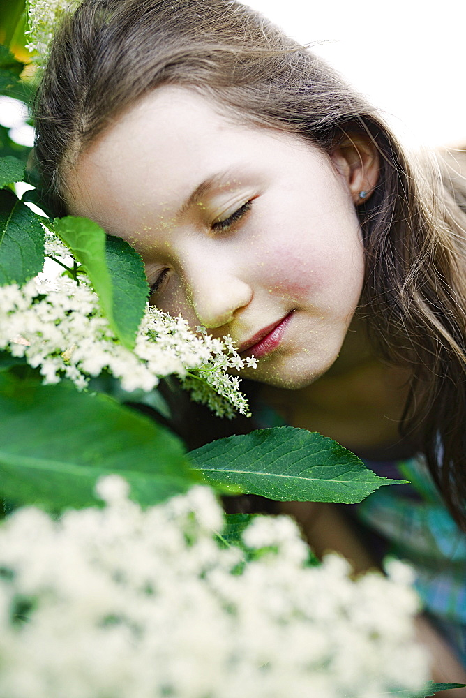 Serene girl leaning on blooming bush
