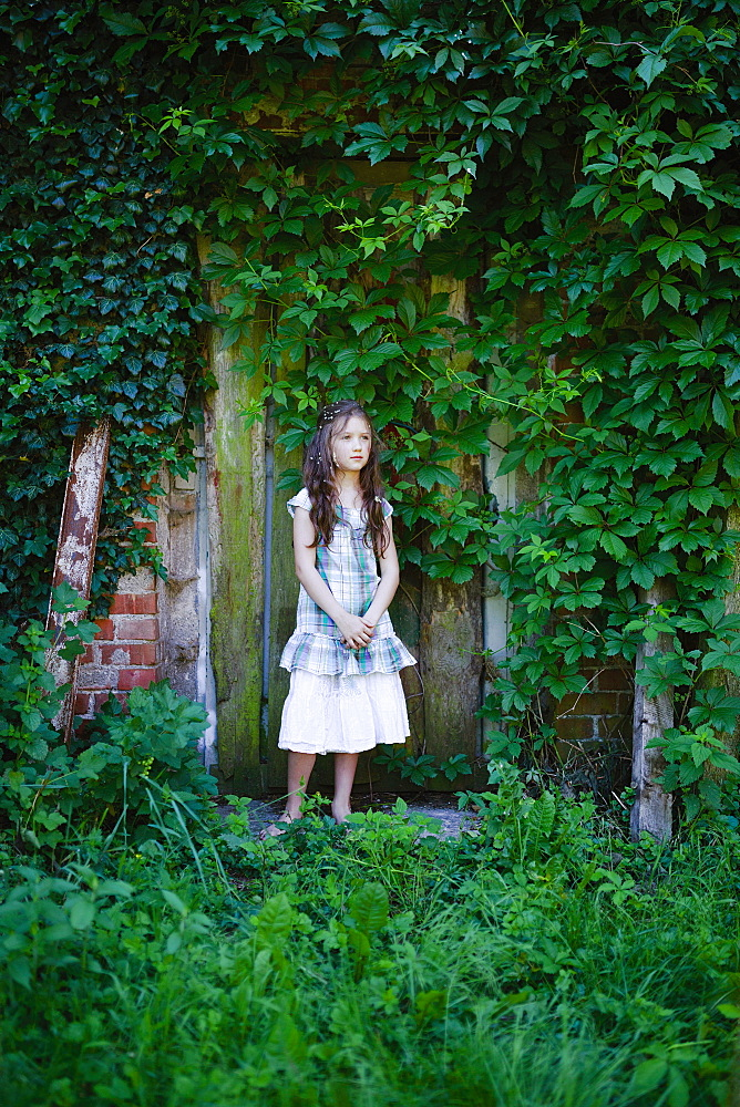 Serene girl in dress standing at rustic door covered with green ivy