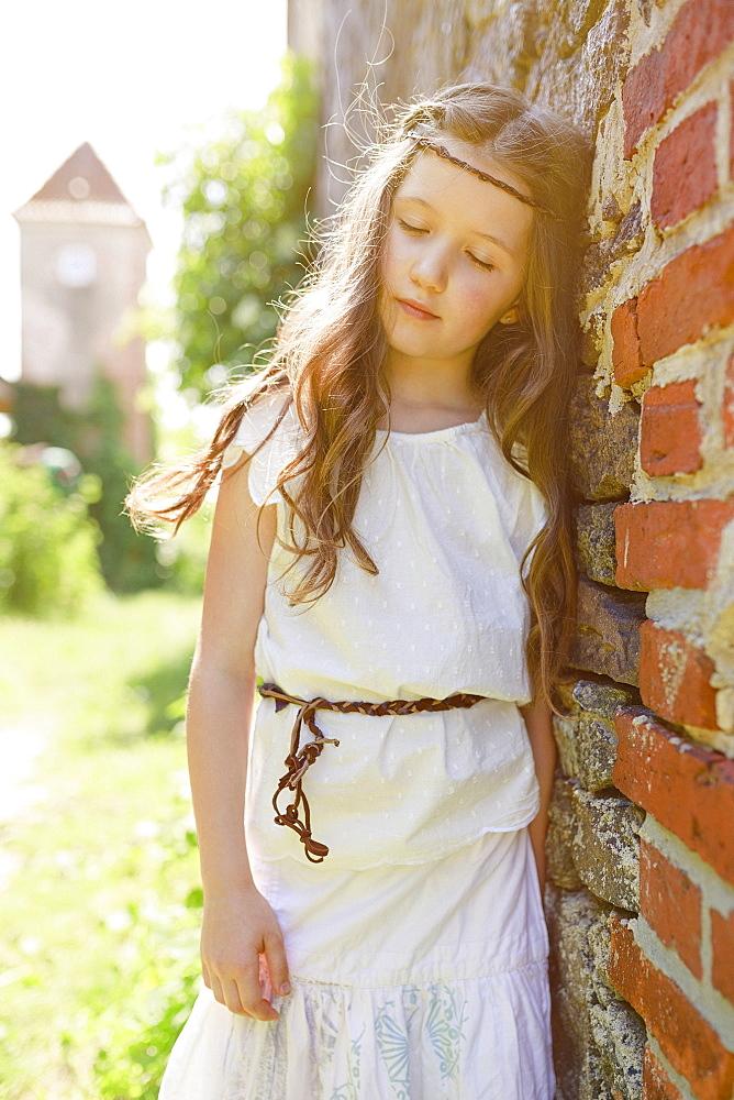 Serene girl in dress leaning against brick wall