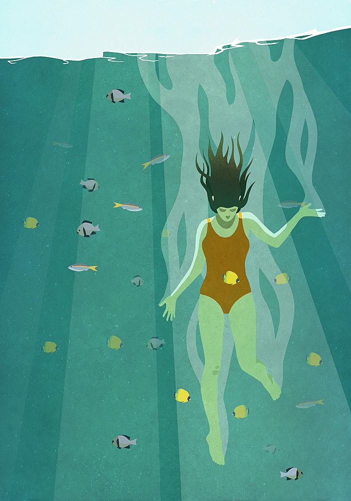 Woman diving into ocean surrounded by fish