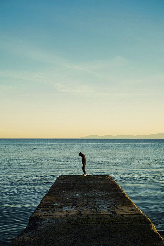 Boy in hoody standing on ocean pier, Victoria, British Columbia, Canada