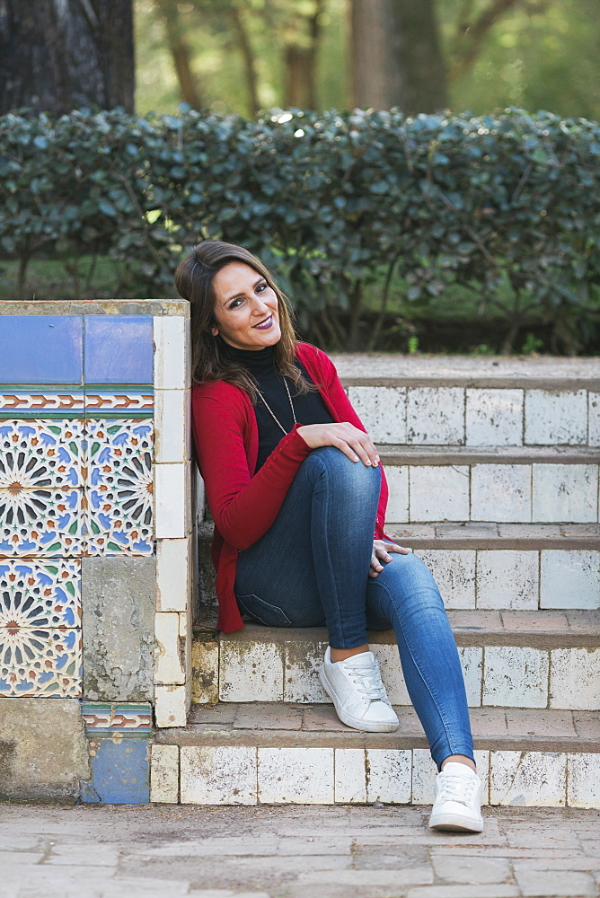 Portrait happy woman sitting on park steps next to mosaic wall