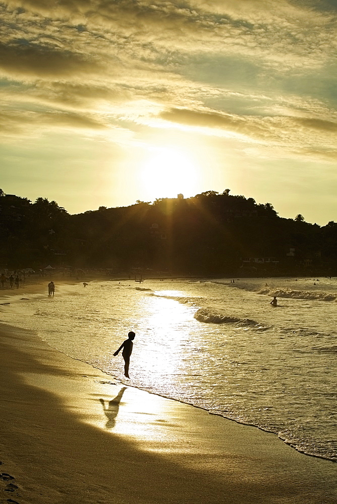 Silhouette boy wading in ocean surf on tranquil beach at sunset, Sayulita, Nayarit, Mexico