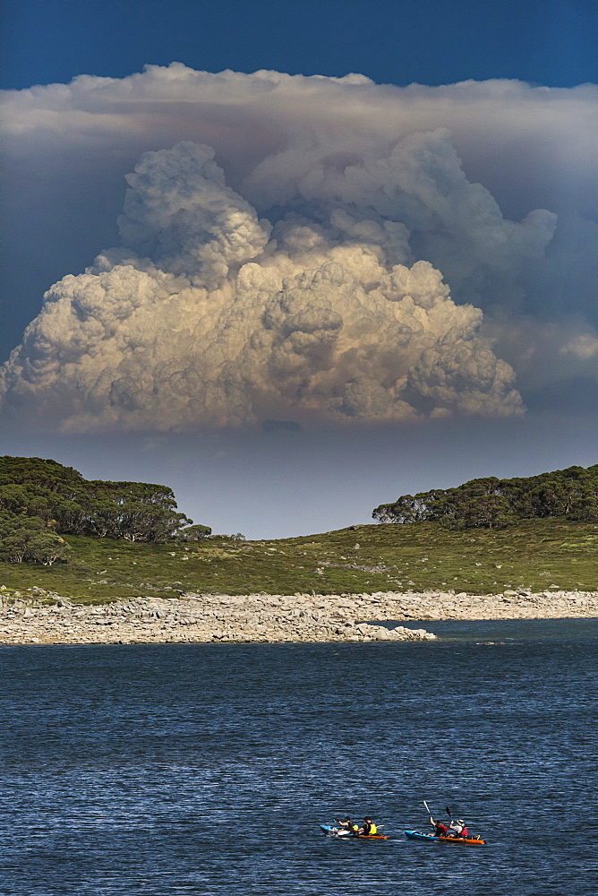 Kayakers on water with bush fire smoke rising in background, Falls Creek, Victoria, Australia