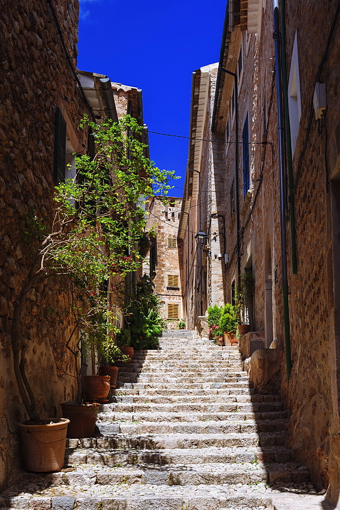 Sunny stone steps between buildings, Fornalutx, Mallorca, Balearic Islands, Spain