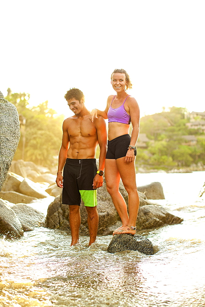 Young, fit couple standing on ocean rocks, Sayulita, Nayarit, Mexico
