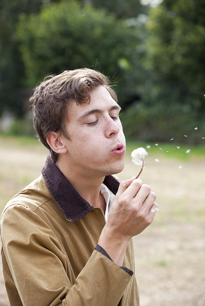 Man blowing dandelion and making wish