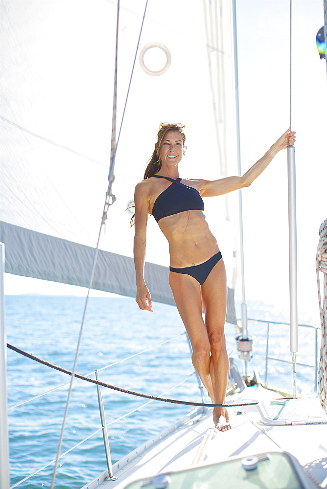 Portrait confident woman in bikini on sunny sailboat