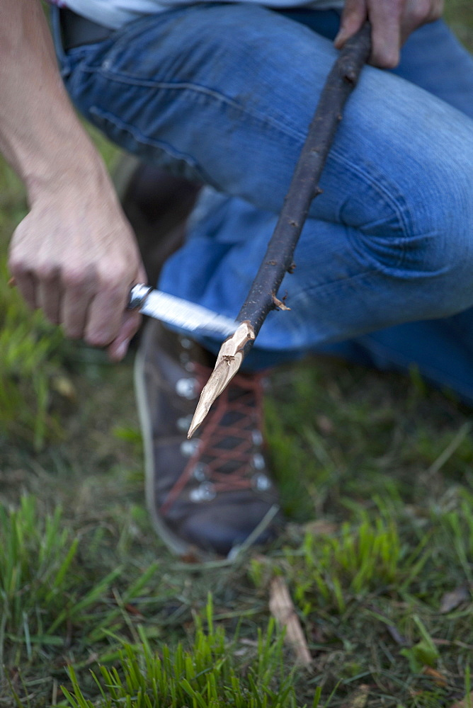 Man cutting stick with knife, close-up