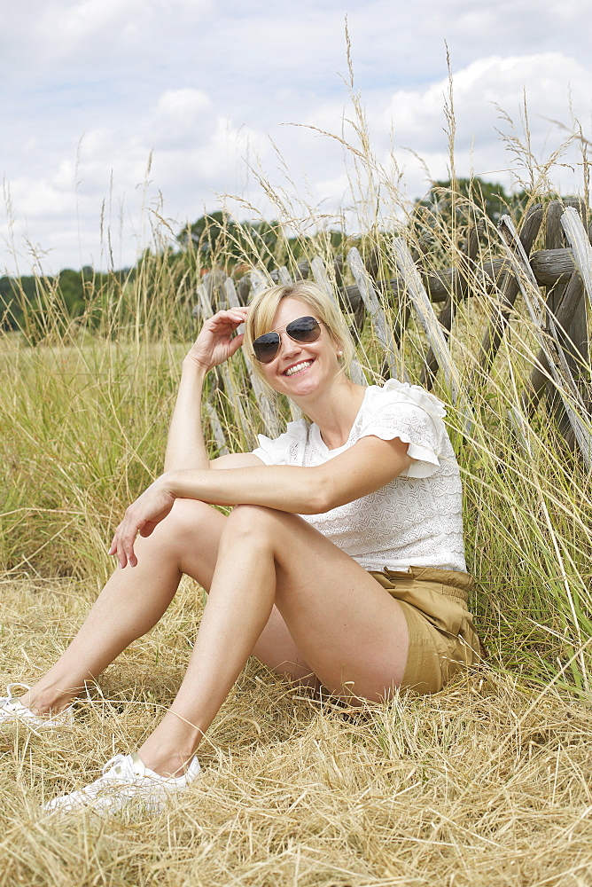 Portrait confident, carefree woman sitting in tall grass