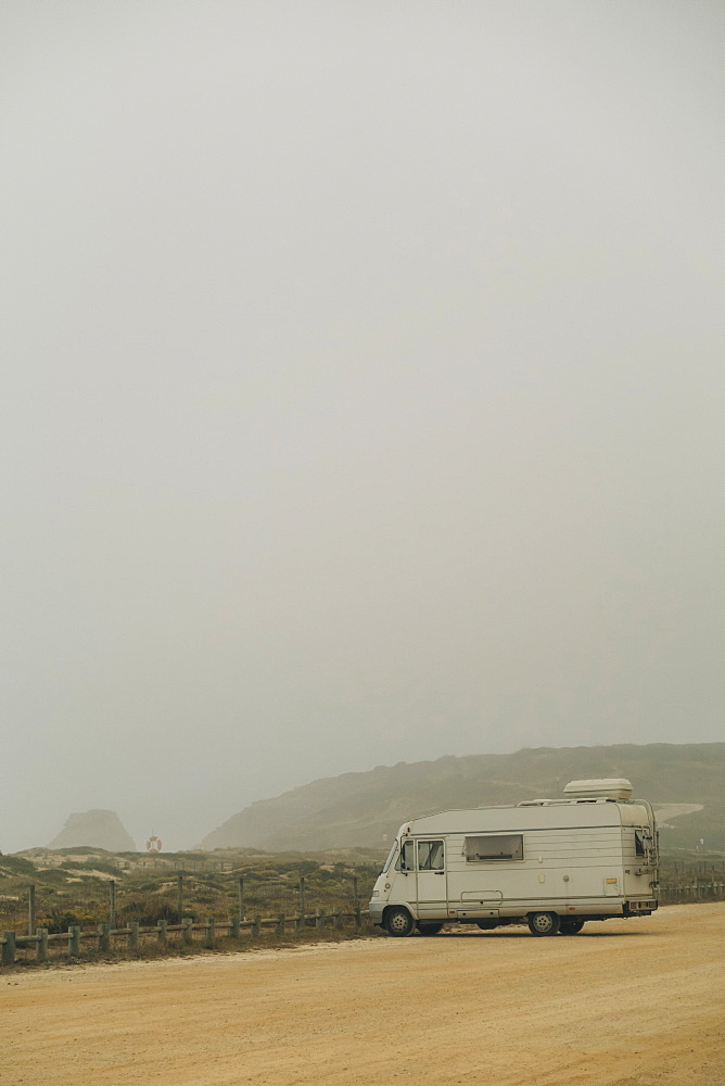 Camper van parked on foggy beach parking lot, Santa Rita Beach, Lisbon, Portugal