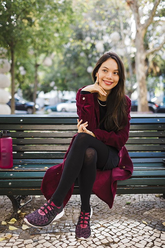 Portrait smiling, stylish woman on park bench