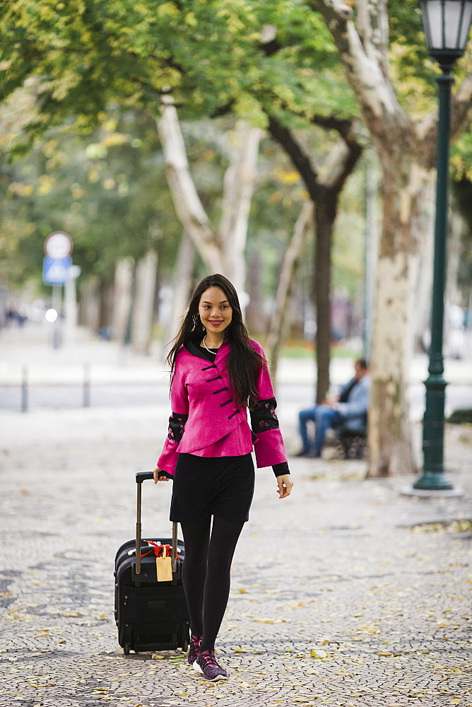 Smiling female tourist pulling suitcase along treelined sidewalk
