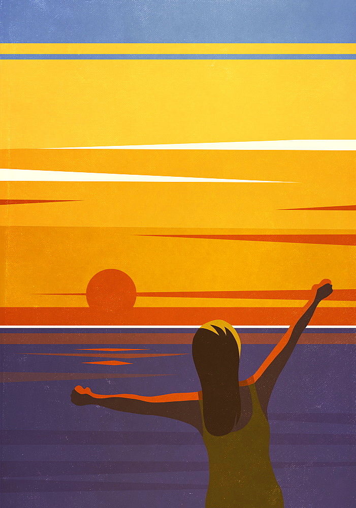 Carefree woman with arms outstretched enjoying sunset view over ocean