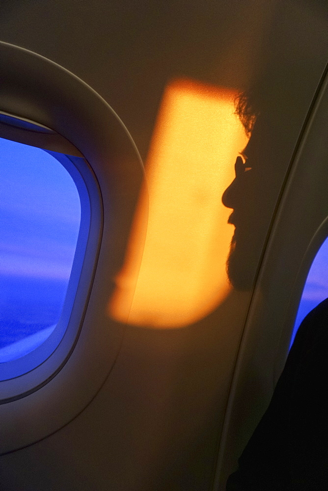 Shadow of man against airplane window